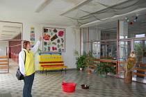 Takhle vypadá vstupní hala do základní školy ve Starém Sedlišti. Návštěvníky vítá lavor vody a promáčené stěny. Na snímku ukazuje spoušť od vody místostarostka Starého Sedliště Jitka Valíčková.