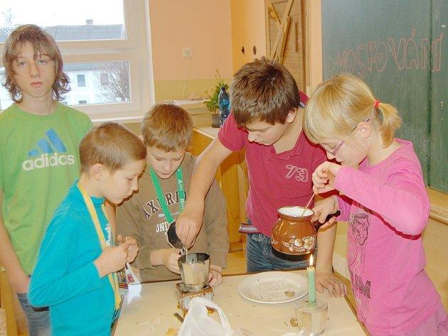 Děti rozehřívají vosk nad plamenem, aby ho mohly následně vlít do formy a vznikla nová svíčka.