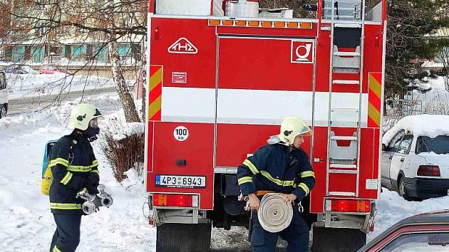 POŽÁR. Hasiči zasahují u pátečního požáru panelového domů v tachovské Zárečné ulici.