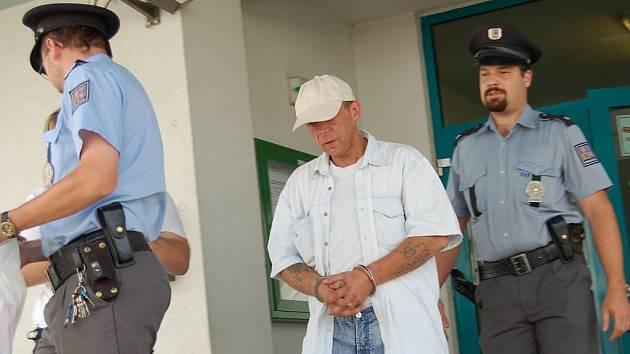 Policisté po výslechu na obvodním oddělení v Tachově odvádějí osmatřicetiletého R. H.