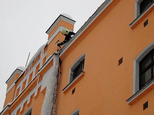 Rampouchy visící ze střechy a led na okapových rourách sundavali dobrovolní haciči z Chodové Plané.