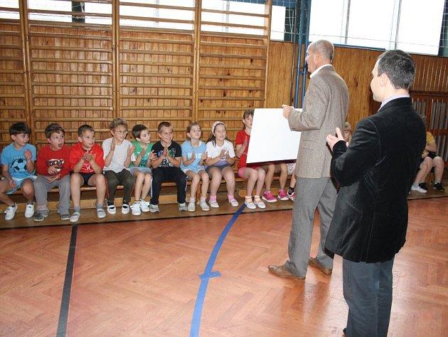Ředitel školy Z. Hnát a šéf dodavatelské firmy P. Ráž ukazují dětem šek na 30 tisíc korun, který Zárečná obdržela.