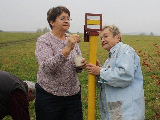 Hana Trávníčková a Marie Mirtlová právě zvýrazňují sloupek se žlutými turistickými značkami mezi Tachovem a Studánkou