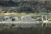 Štěrk na březích Labe u Neštěmic pochází z koryta. Povodí ho vytěžilo po loňských povodních. Vodohospodáři čekají na dotace, aby ho za pomoci člunů odvezli.