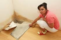 Veronika Dadučová ukazuje zdi plné plísně od špatně odizolovaného zdiva zvenčí domu. Bydlení ve startovacích bytech trápí nájemníky od samého počátku. Rok a půl ale jejich stížnosti nebral nikdo vážně. Nyní obec práce reklamovala.