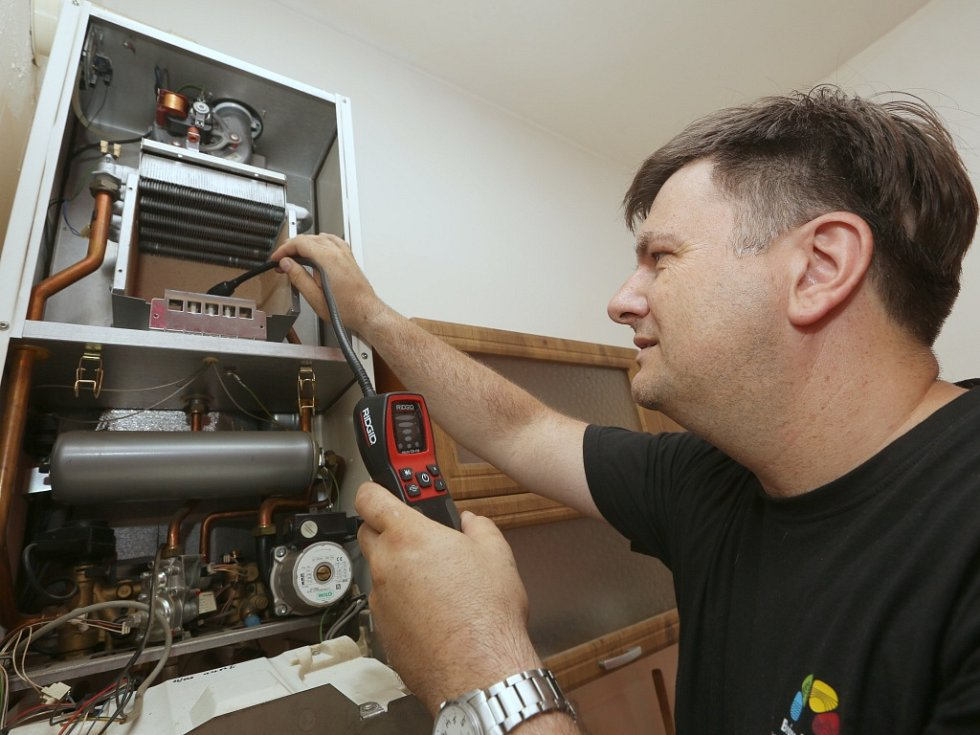 Plynař Karel Černý při kontrole plynového kotle.