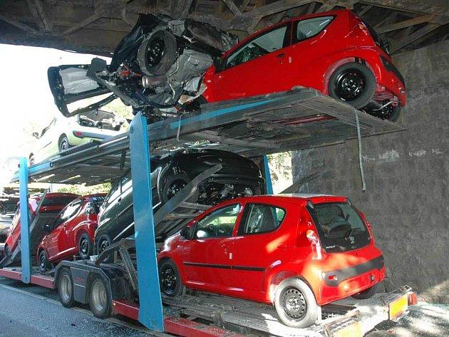 NOVÁ AUTA NA ŠROT. Řidič litevského kamionu s úplně novými auty neodhadl svoji výšku nákladu a zasekl se v Teplicích pod mostem. Nejen že zničil řadu vozů, ale také zastavil dopravu na železnici.