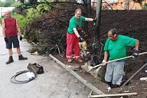 Dělníci opravují veřejné osvětlení, poškozené plameny.
