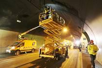 Dělníci opravují v tunelu dálnice D8 Panenská část elektroinstalace a čistí signalizační prvky od nánosu sazí.