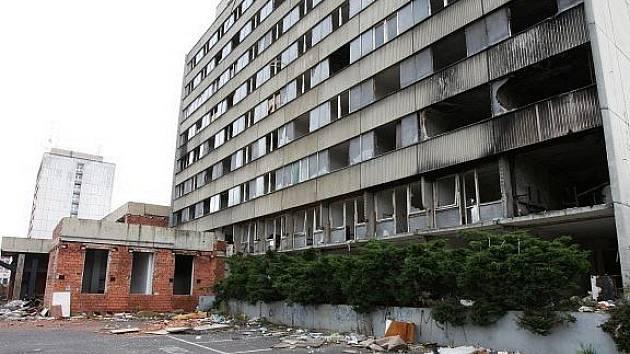 Hotel Máj: listopad 2010. Okna jsou už téměř všechna vymlácená, některé zdi se bortí, ty další jsou ohořelé. Všude kolem se válí odpadky od bezdomovců.