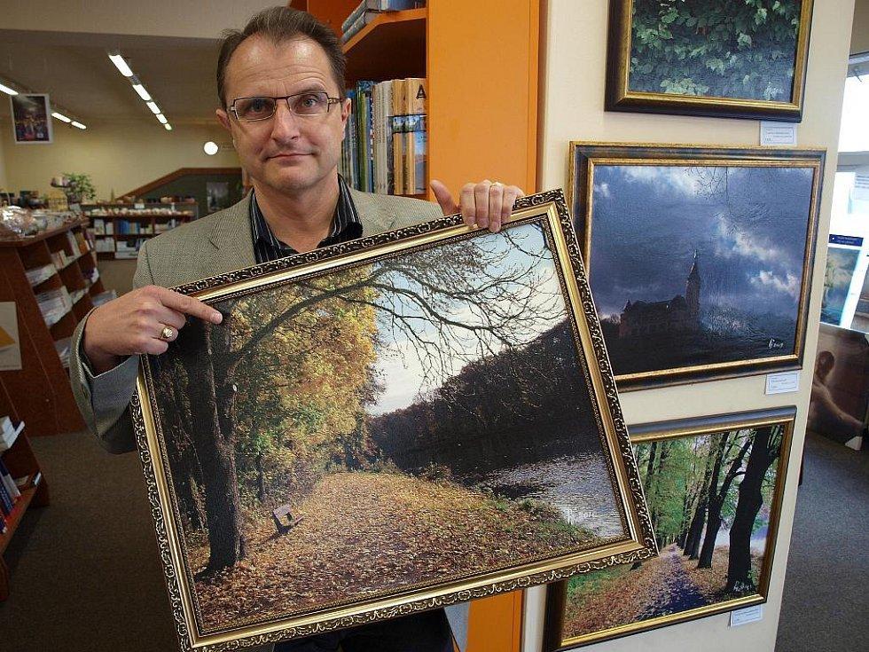 Pavel Mészáros ukazuje Labské nábřeží v Poděbradech na výstavě svých fotoobrazů v knihkupectví Beran v Ústí nad Labem.