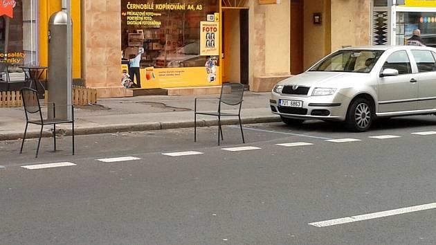 Kancelářské židle blokují parkovací místo v Pařížské ulici. Aby si někdo mohl parkoviště takto zabrat, musí mít povolení odboru dopravy. Jinak riskuje pokutu.