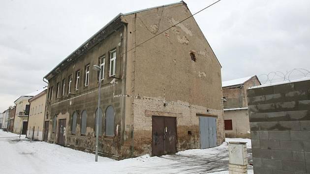 Kolem místa bývalé školy dnes stojí ubytovna a vysoká zeď.