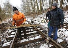 Členové sdružení Muzeální železnice v Zubrnicích dělají údržbu na kolejovém svršku. Vyměňují část poškozených pražců a nahrazují je novými.