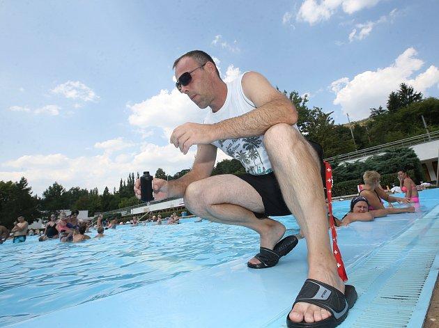 Provozní vedoucí areálu v Brné Petr Urban odebírá vzorek vody z bazénu kde k problému s kálením došlo.