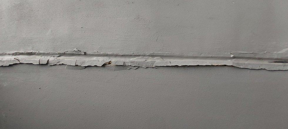 Podchod v Nové ulici na střekovském Kamenném Vrchu. Štuky a malba praskají, odchlipují se.