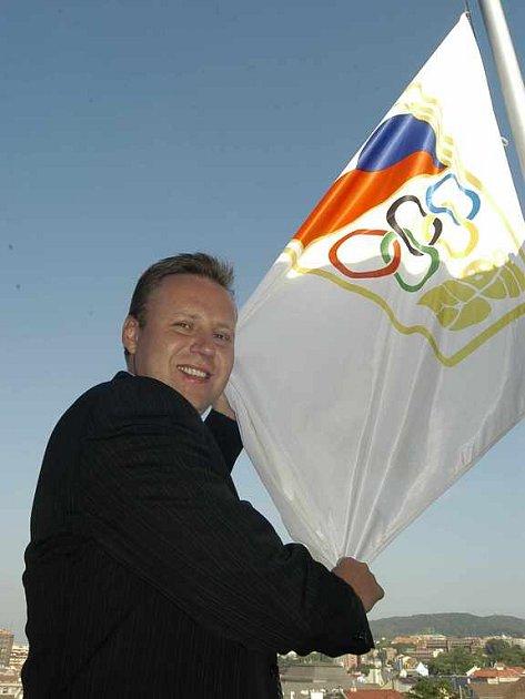 Primátor Jan Kubata vyvěšuje olympijskou vlajku