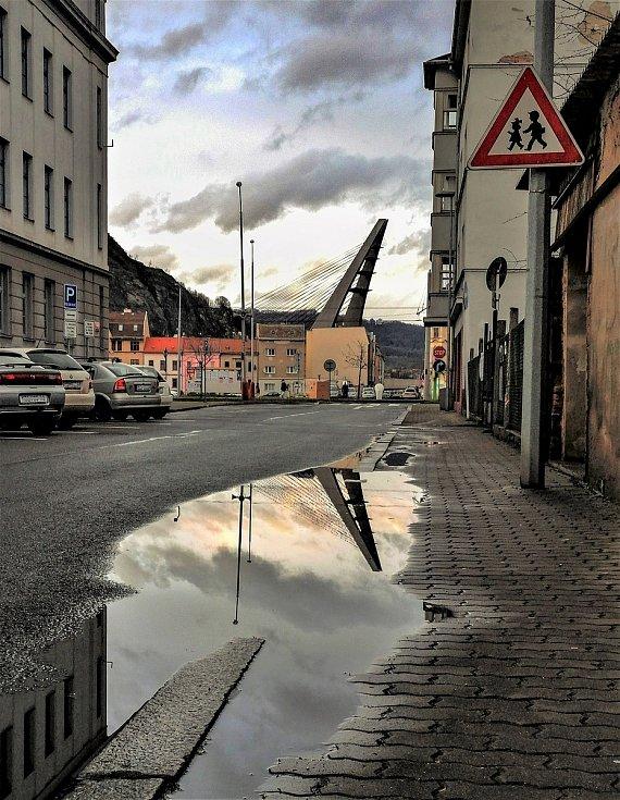 Ústecký fotograf Martin Vodňanský si oblíbil snímky zachycující dominanty města nad Labem v odrazu kaluže. Říká jim loužovky. Na snímku je Mariánský most.