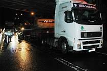 Řidič tahače přepravující bagr na návěsu, podcenil podjezdovou výšku železničního mostu ve Střelecké ulici a stavební stroj doslova napasoval pod most.