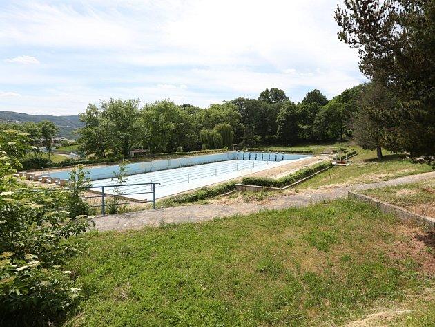 Venkovní bazén na Klíši je vypuštěný a uzavřený. Postupně zarůstá trávou a plevelem.