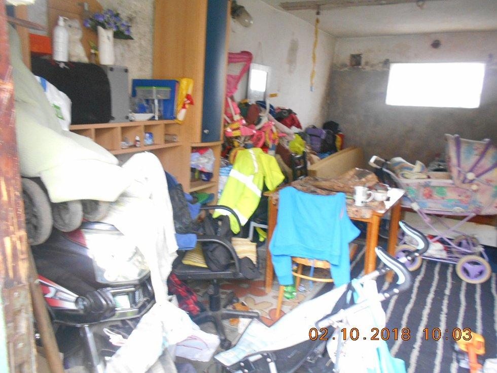 Garáž, kterou matka s dětmi obývala. Nejsou zde odpovídající hygienické podmínky, chybí voda i toaleta.