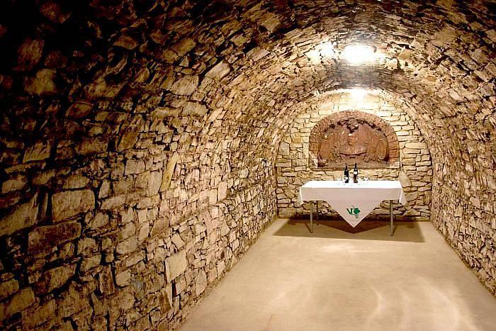 Spodní část konce chodby sklepení s reliéfem tehdejšího majitele vinárny Eduarda Lorenze z roku 1906.