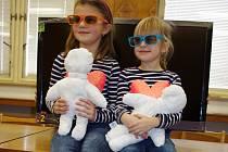 Na vítězné fotografii Děti pod stromečkem byla Kačenka (vpravo) a Sárinka, jejíž sestra Sabina je fotografovala. Děti sedí před televizorem, který věnovaly ústecké nemocnici.