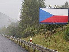 Bilbordy u dálnice se státní vlajkou.