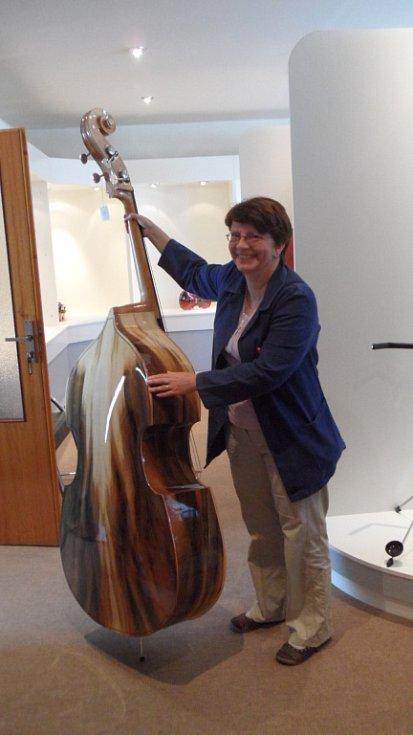 Hlavní technolog Hana Tylšarová ukazuje jeden z výjimečných nástrojů vyrobených v Lubech. Jde o basu s unikátním zbarvením použité dýhy.