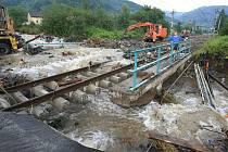 Obec Těchlovice: Obrovské kameny, písek a hlínu nyní odklízí těžká technika, ale stále přitékající voda komplikuje čištění tratě.