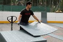 Dělníci instalují na Stadionu mládeže nový plastový povrch.