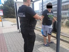 Žena kouřila na zastávce MHD.