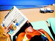 Čtenářka na dovolené s Libereckým deníkem.