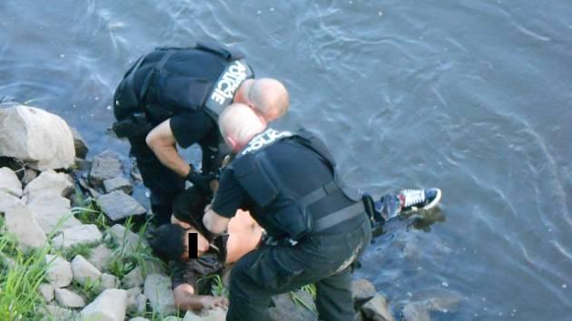 Strážníci muže vytáhli z vody na břeh.