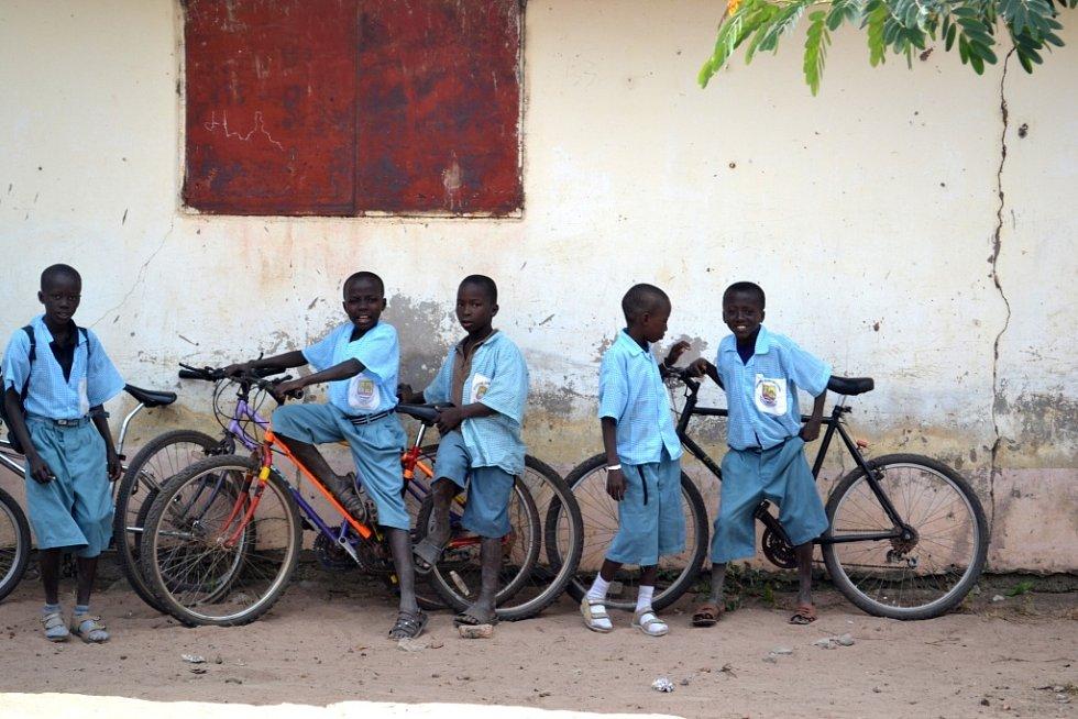 Děti s koly u školy.