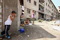 Vnitroblok domů ve Sklářské ulici je plný odpadků. Mezi nimi si hrají děti.
