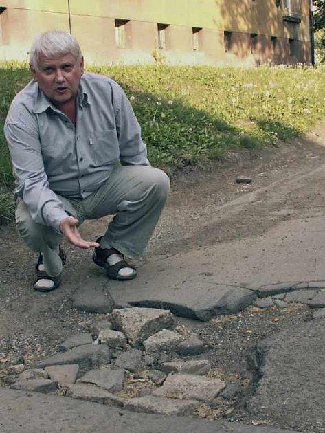 Pavel Rypáček nad jedním z výmolů ve vozovce