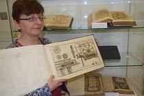 Starý tisk předvádí Helena Houfková z muzejní knihovny.