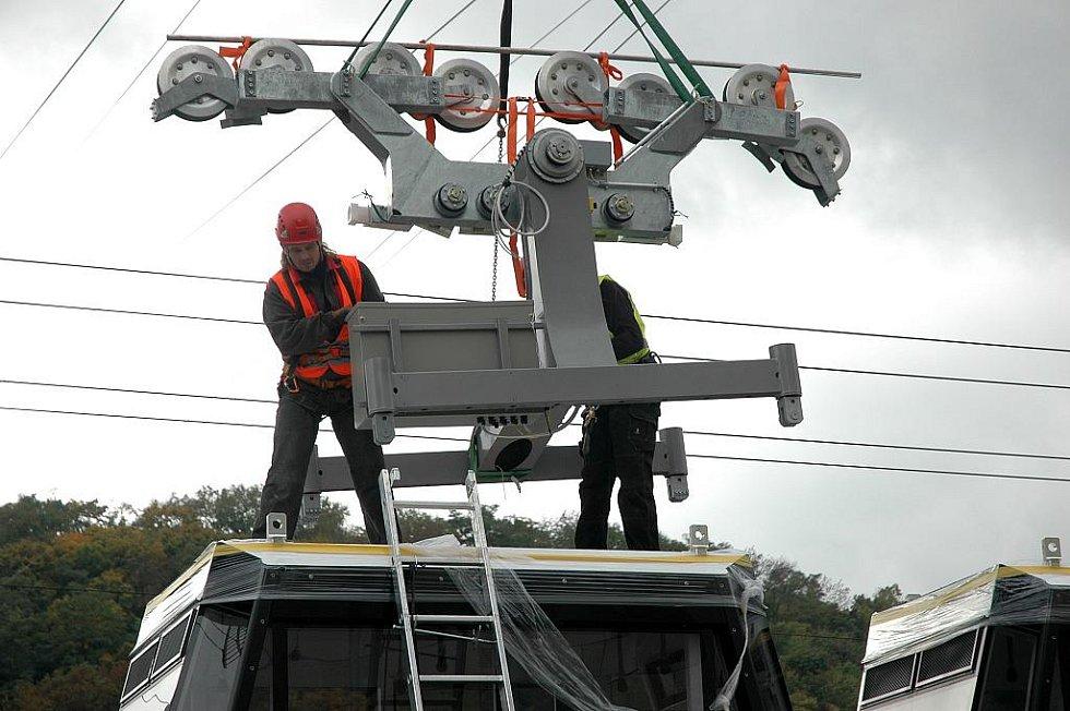 Instalace a usazování kabinek nové lanové dráhy.