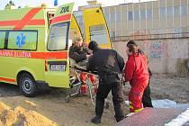 Záchranáři odvážejí do nemocnice bezdomovce přímo z parovodního průduchu z Veleslavínovy ulice.
