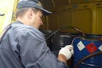 Celník odebírá vzorky kapaliny ze zadržených sudů.