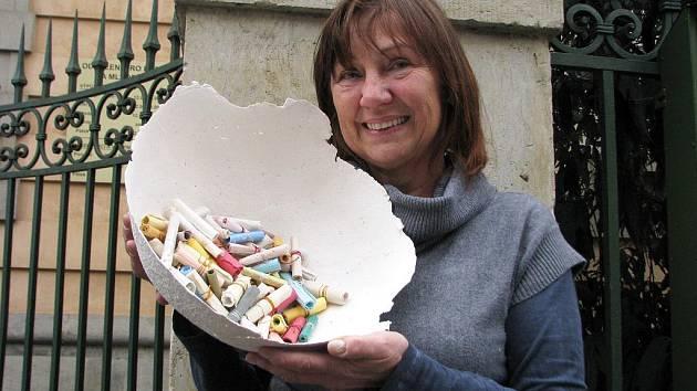 Mísa se svitky z ručního papíru, jeden z netradičních artefaktů výstavy v knihovně v Ústí. V rukou ji drží a ukazuje ji Irena Štyrandová z litoměřické Dílny ručního papíru.