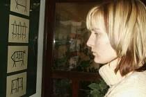 Kristýna Dúlová, studentka UJEP, si prohlíží vystavovaná výtvarná díla.