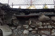Zhroucená zeď ohrožuje dům.