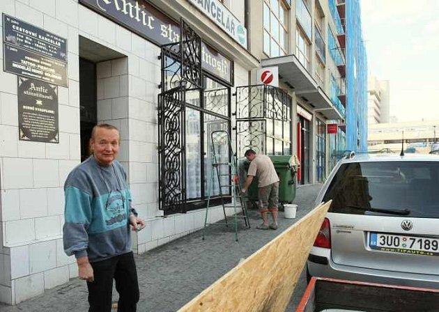 Majitel starožitnictví Václav Kovařík při sundavání ochranných desek, které měly obchod chránit před případným poškozením při pochodu nacionalistů