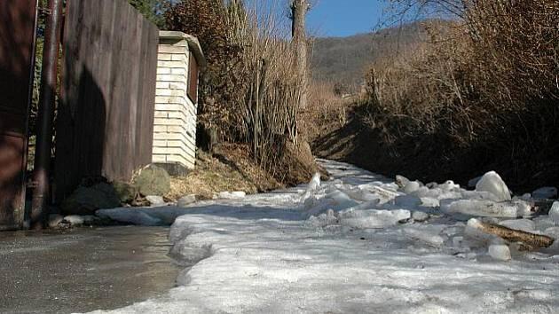 Obyvatelé domů kolem Bedlové ulice se k domu autem nedostanou. Nákup musejí tahat ledovým korytem v batohu. Led cestu pokrýval i včera, kdy se okolní kopce zelenaly.