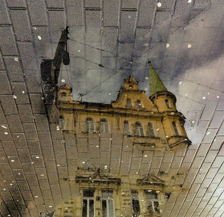 Ústecký fotograf Martin Vodňanský si oblíbil snímky zachycující dominanty města nad Labem v odrazu kaluže. Říká jim loužovky. Na snímku je budova Komerční banky