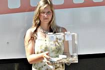 Hosteska Tereza Počtová ukazuje kasičku s dobrovolným vstupným.