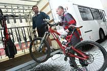 Řidič Milan Tichý nakládá do vleku cyklobusu kolo jednoho z cestujících cyklistů.