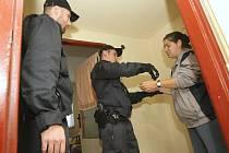 Policisté po kontrole odvádějí v poutech celostátně hledanou ženu.